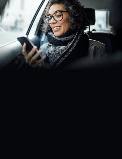 Woman in car smiling at phone