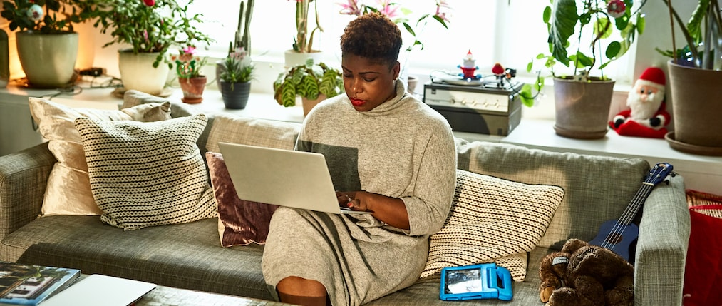 Mid adult woman typing on computer in living room, remote working, freelancer, Christmas season