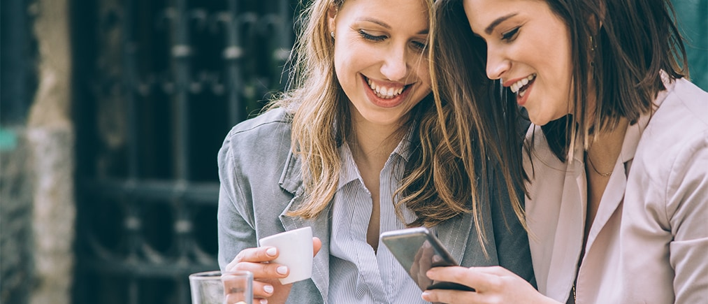 Two beautiful young woman sitting at cafe drinking coffee and looking at mobile phone