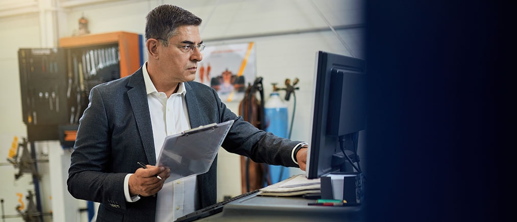 Mid adult inspector analyzing data while using computer in auto repair shop.