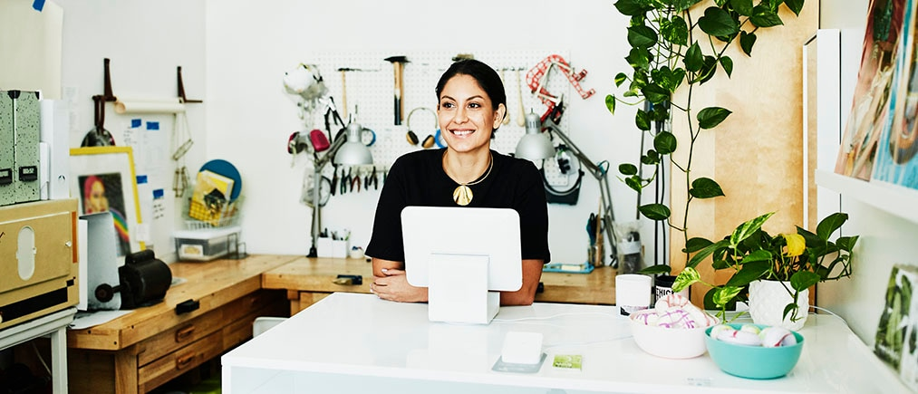 Smiling female business owner standing behind counter in boutique