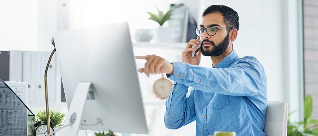 Shot of a young designer talking on a cellphone while working on a computer in an office