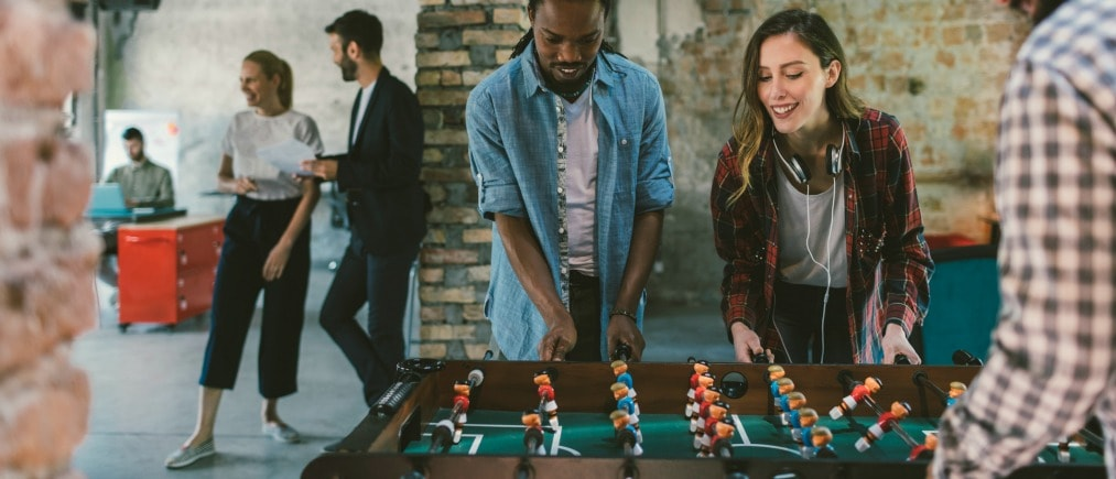 Coworkers playing foosball on break. They are having fun on break and enjoying the game