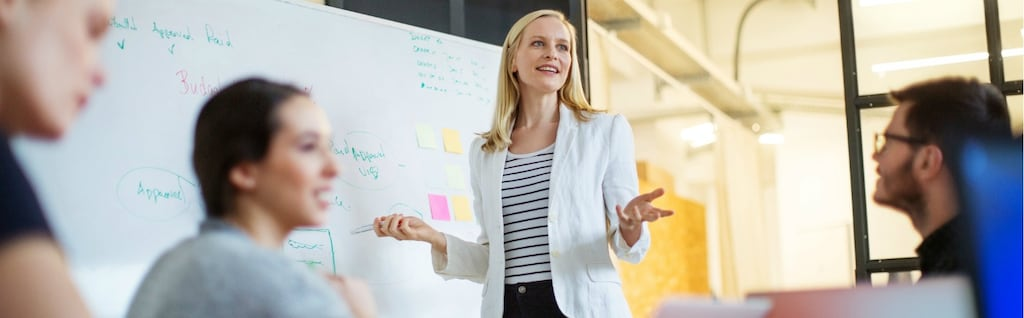 Young businesswoman giving presentation on future plans to her colleagues at office
