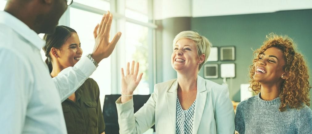 Shot of businesspeople high fiving in an office
