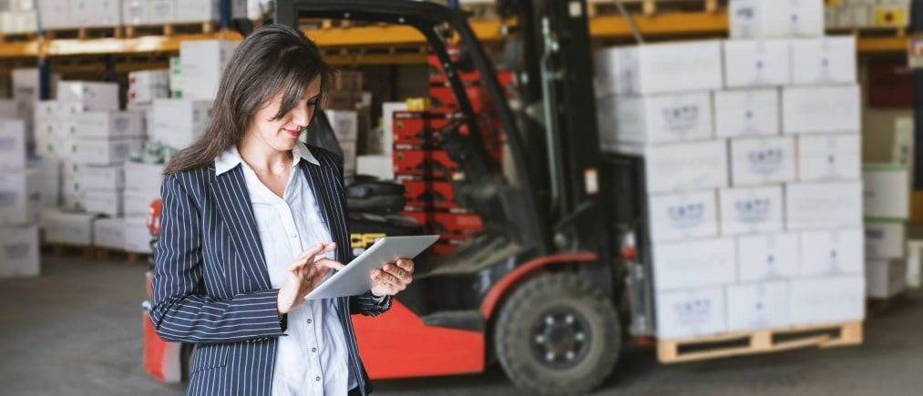 Happy industrial Businesswoman with suit working with tablet pc  in distribution warehouse
