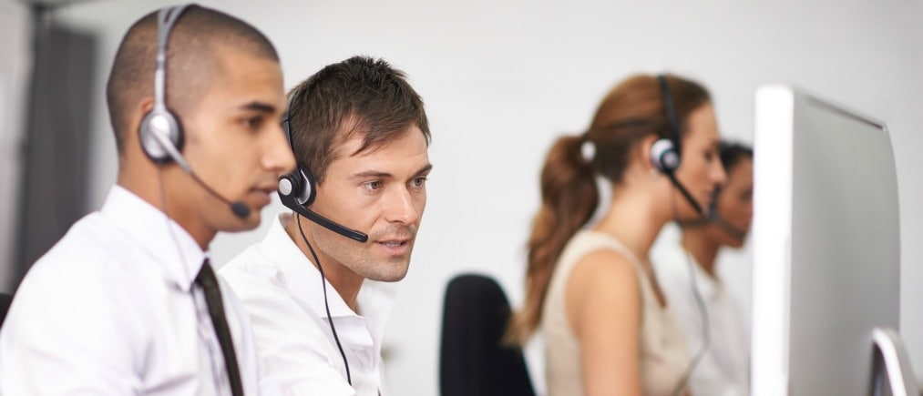 Shot of a group of help desk operators wearing headsets and working in an office