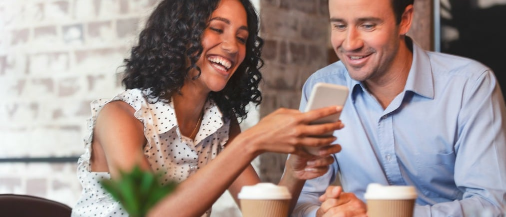 Businessman and businesswoman looking at a mobile phone. Multi ethnic group with African American and Caucasian. They are casually dressed and having a discussion. They are drinking coffee, laughing, smiling and having fun. Could be reading or sending a text message.