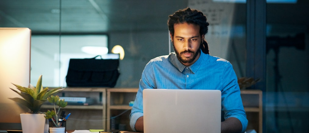Cropped shot of a young designer working late on a laptop in an office