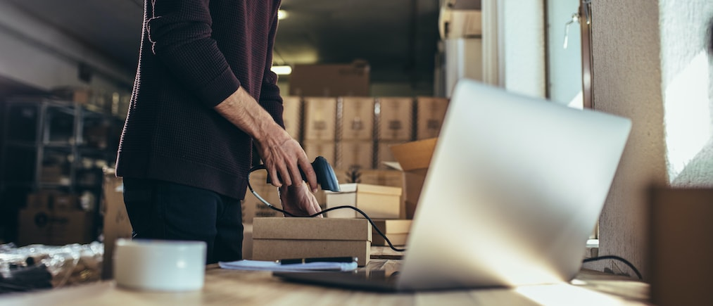 Cropped shot of man scanning the barcode of the shipment at his desk. Man working in a drop shipping office, preparing a parcel to deliver to the customer. (Cropped shot of man scanning the barcode of the shipment at his desk. Man working in a drop sh