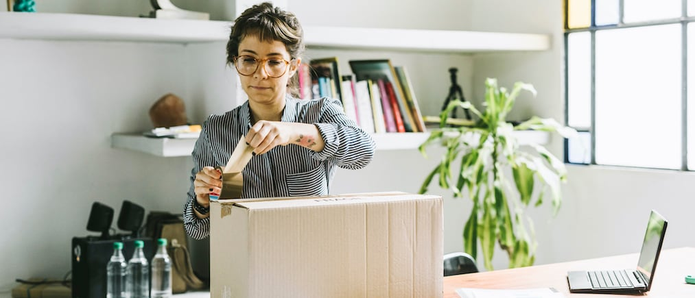 Young woman closing a cardboard box with a tape to send it to a customer.