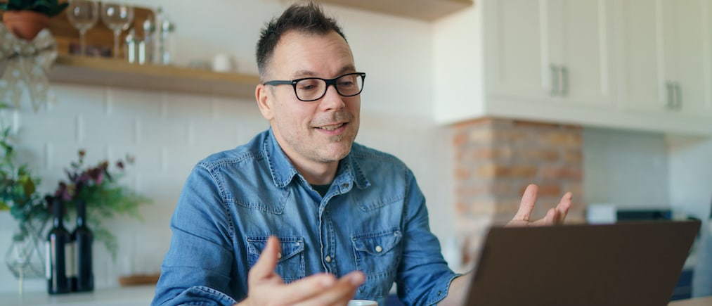 Happy adult man having a video call with a laptop