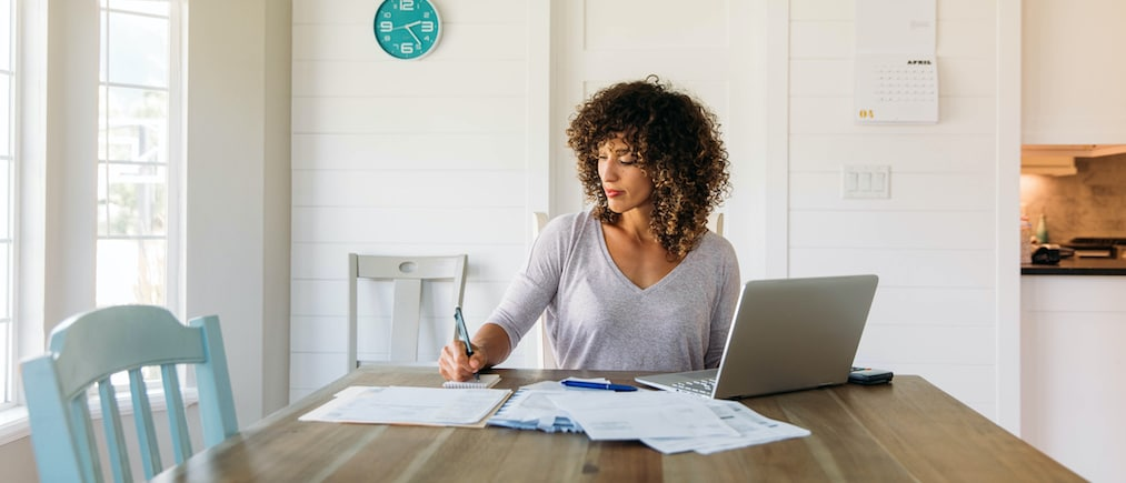 A woman sits at her dining room table with laptop and financial reports doing her monthly budget. She is writing down budgets as she works on her computer to do monthly finances, pay taxes and save money for the future.