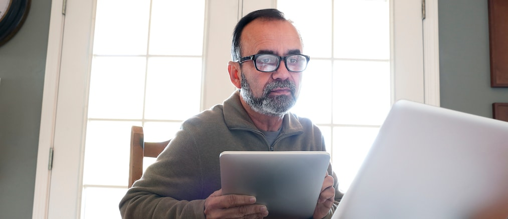A hispanic man in his mid fifties sits at his dining room table and peers through his glasses while he holds a digital tablet and looks at his laptop computer. The table is strewn with his work as the morning sun streams in from outside and through th
