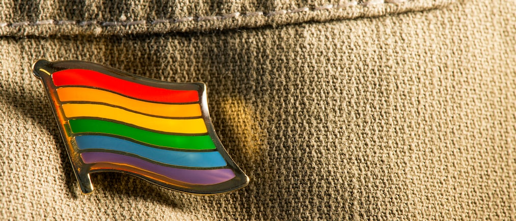 Gay pride flag lapel pin on a brown jeans shirt.