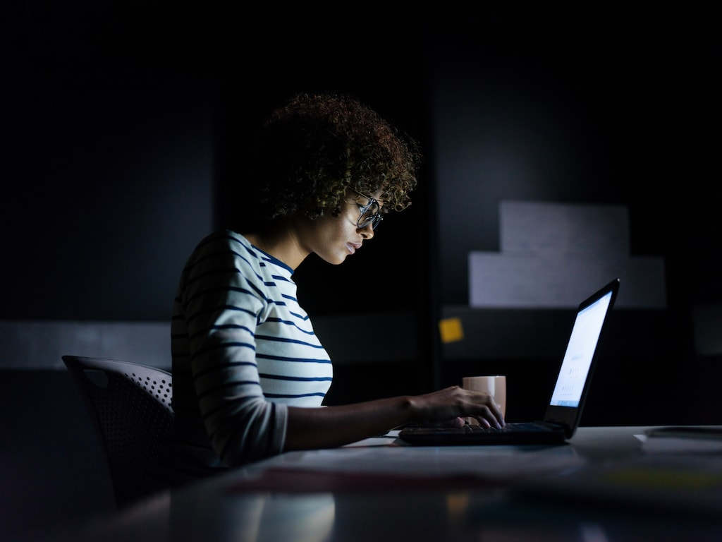 A businesswoman staying late hours in the office concentrating on her work sitting with a laptop and typing.