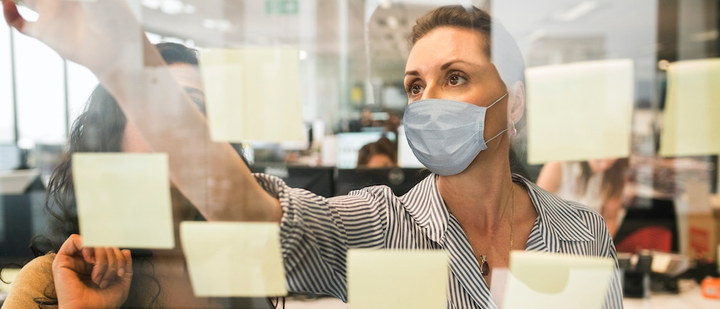 Businesswomen working together behind a glass wall with reflections wearing a healthcare face mask.