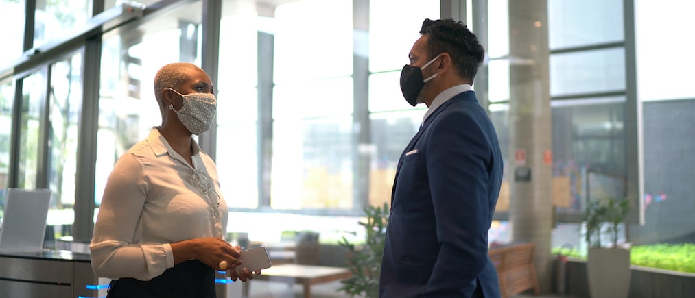 Coworkers talking on office's lobby - with face mask