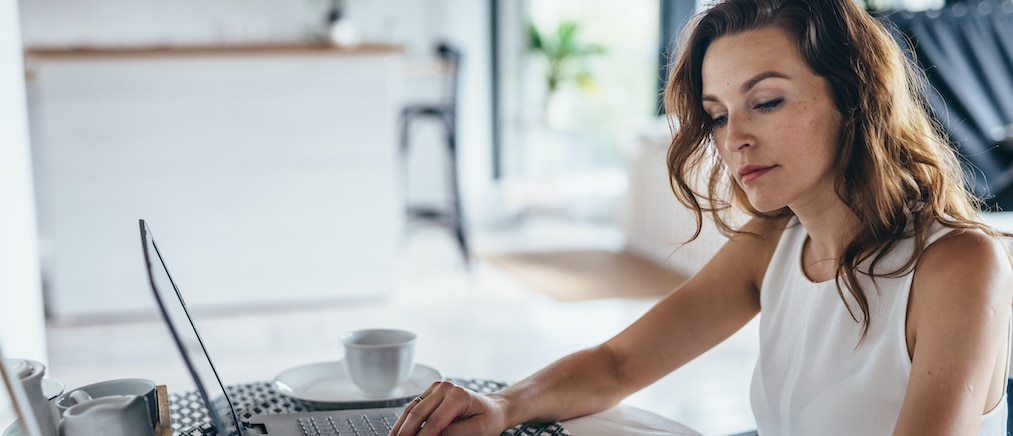 Woman using laptop while sitting at table. Young businesswoman sitting in kitchen and working on laptop