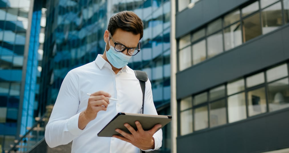 Businessman with protective face mask using digital tablet outdoors