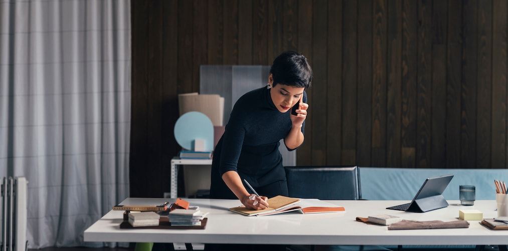 Beautiful Latin American interior designer in a black outfit making a phone call and writing something down at her office (copy space).