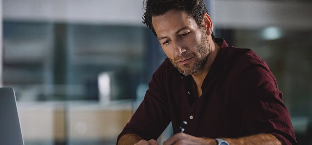 Cropped shot of a handsome mature businessman sitting alone in his office and writing out notes