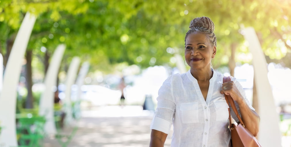 While walking through a city park, a beautiful female tourist with gray hair smiles with satisfaction.