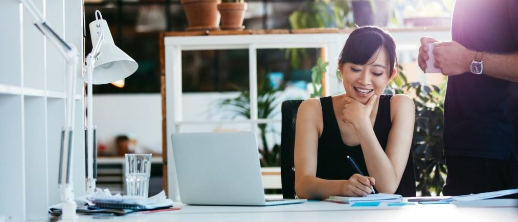 Shot of smiling asian businesswoman writing notes on notepad with colleague standing by. Female executive working at her desk with laptop taking notes.