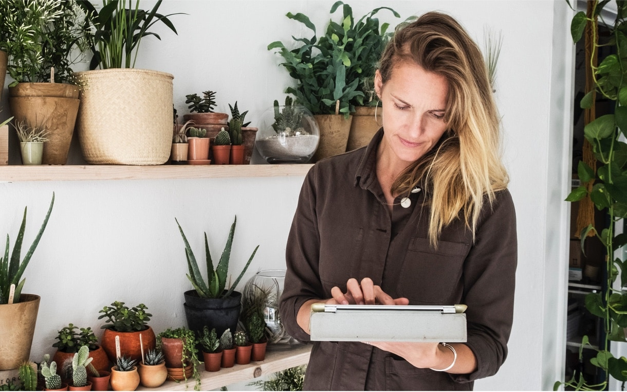 A woman holding a tablet with a shelf of potted plants behind her