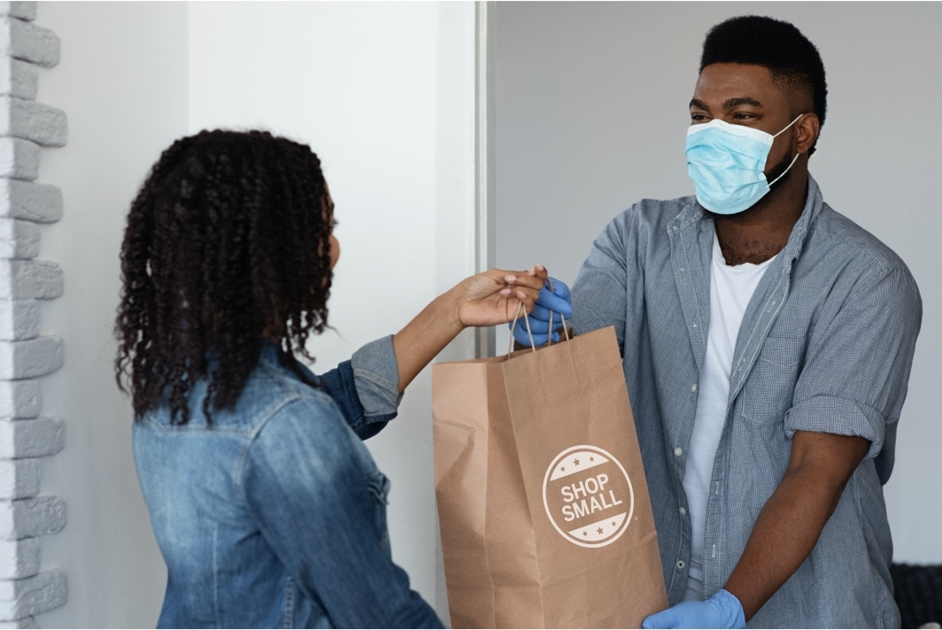 Delivery man wearing gloves and a mask delivering a takeout bag to a woman