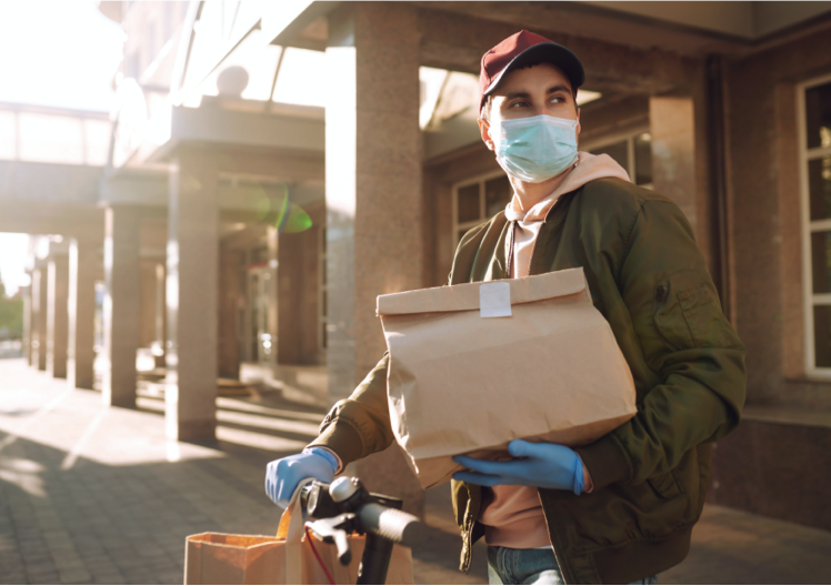 A man wearing mask and gloves holding food takeout bags