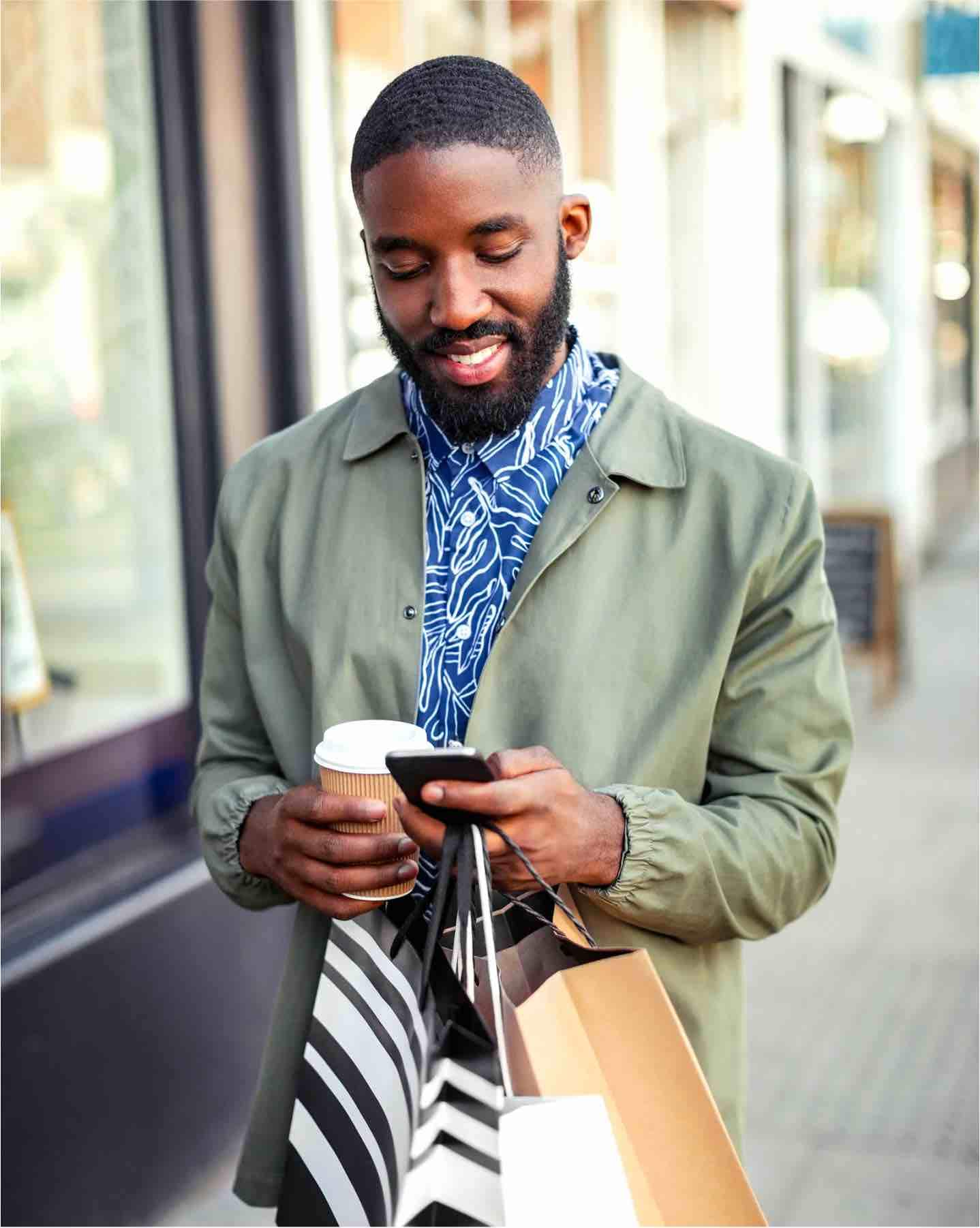 A man walking outside carrying shopping bags and looking at their phone